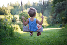 A Small Child Swings On A Swin...