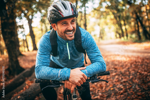 Young man biking through forest
