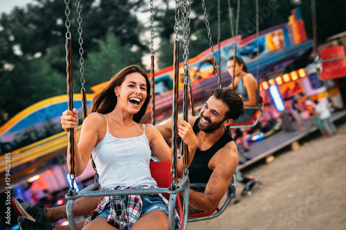 Young couple enjoying on the swings