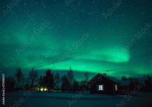 Foto auf Gartenposter Nordlicht Northern lights (Aurora Borealis) over cottage in Lapland village. Finland