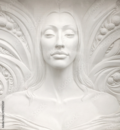 Bas-relief sculpture of a young woman face with tall neck, long hair, and bare s Wallpaper Mural