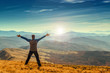 Happy man standing on the top of the mountain with raised arms