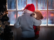 Child With A Toy Bear On His Hand Looking At The Christmas Window