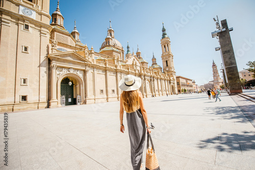 Young woman tourist walking near the famous cathedral on the central square during the sunny weather in Zaragoza city, Spain