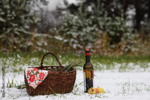 Keuken foto achterwand Picknick Picnic in the field on the first snow. The composition includes red wine, oats, apples.