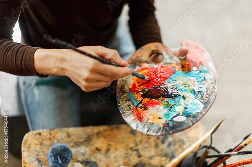Obraz na płótnie Caucasian artist putting red paint on his palette in the studio
