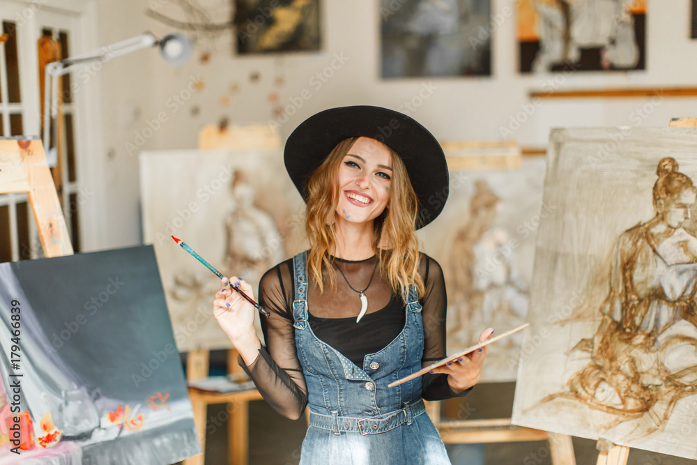 Fototapeta Female artist wears black hat posing near picture indoor the studio
