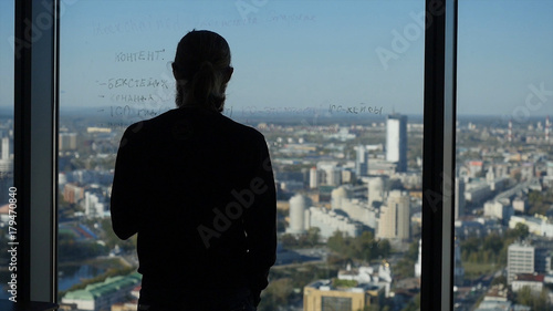 Young businessman is holding a banana and stays at panoramic window Wallpaper Mural