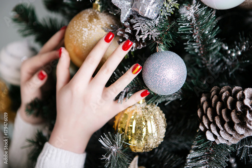 Foto op Canvas Manicure Manicure for the New Year in red against the background of Christmas trees and Christmas toys
