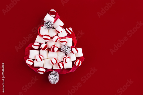 christmas tree shape made of marshmallows and ribbon sweets on red colored background flatlay