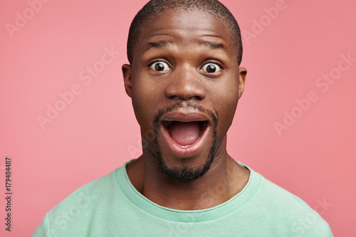 Fotografie, Obraz  Excited dark skinned man opens mouth widely being shocked and glad, rejoices positive news about extreme pay rise