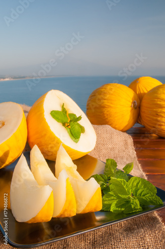 Typical mediterranean fruits: yellow melon with blue sea and Mount etna in the background