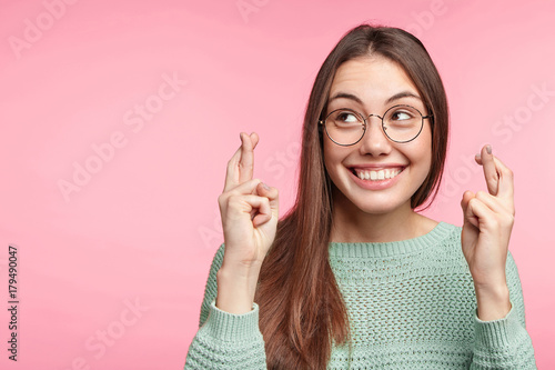 Obraz Indoor shot of glad brunette woman wears spectacles, smiles broadly, keeps fingers crossed, hope for good luck during long trip, isolated over pink background with copy space for your text or hearder - fototapety do salonu