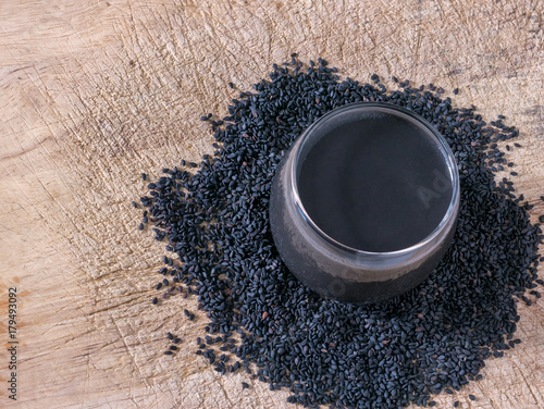 Black sesame drinking in cup with sesame seed on chopping block