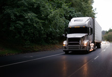 Modern Big Rig Semi Truck With Guard And Turn On Headlights And Reefer Semi Trailer On Evening Road