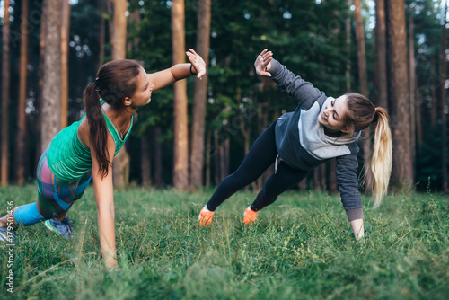 Fotografie, Obraz  Two female buddies doing partner side plank giving high five while training in t