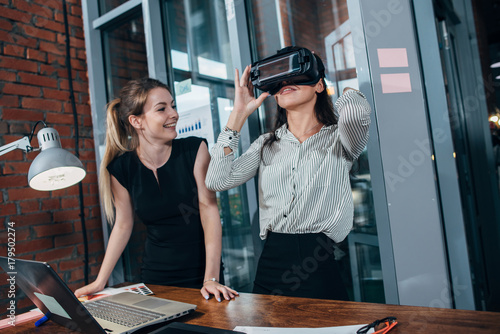 Staande foto Vlees Two female application developers testing a new app designed for VR headset standing in modern office
