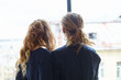 Back view of young female with long wavy hair and male with dreadlocks and flesh tunnels standing close to each other at large window ar home and looking outside, enjoying happy moments together