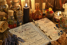 Magic Book With Spells, Lavender Bunch And Black Candle On Witch Table.