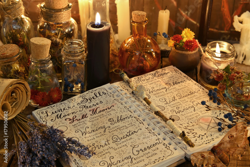 Magic book with spells, lavender bunch and black candle on witch table Wallpaper Mural