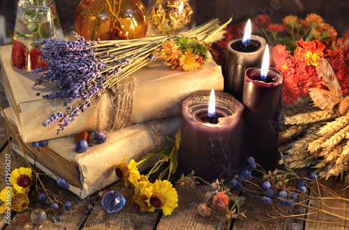 Three black candles, lavender bunch, healing herbs and flowers on planks