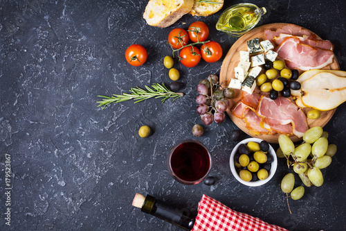 Photo Appetizer, italian antipasto, ham, olives, cheese, bread, grapes, pear and wine on dark stone background