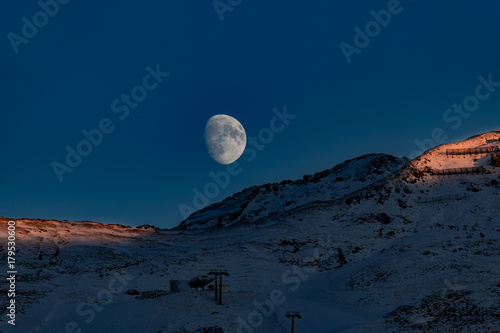 panoramic view of a chairlift in the alps with alpenglow and rising moon плакат
