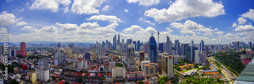 Panorama view of Kuala Lumpur city skyline with dramatic cloud formation and blue sky Wallpaper Mural