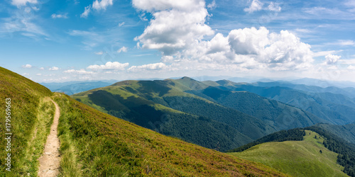Foto op Aluminium Blauw beautiful mountainous landscape on fine summer day. footpath running through grassy hillside under blue sky fluffy clouds. gorgeous panorama of mountain ridge