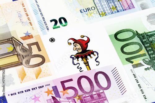 Foto  Spielkarte Joker zwischen Banknoten