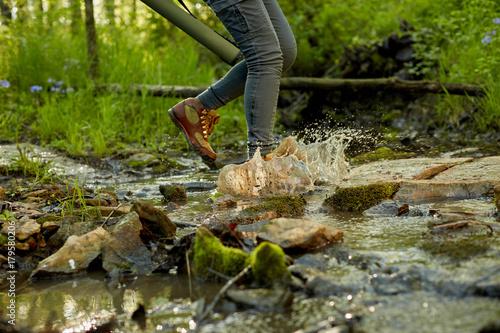 Fotografie, Obraz  Female hiker splashing through a forest stream