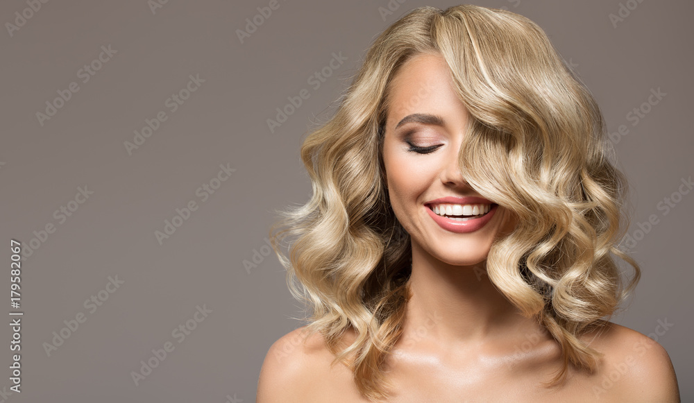 Blonde woman with curly beautiful hair smiling on gray background.