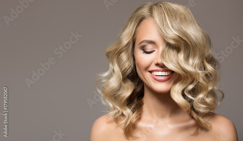 Fotobehang Kapsalon Blonde woman with curly beautiful hair smiling on gray background.
