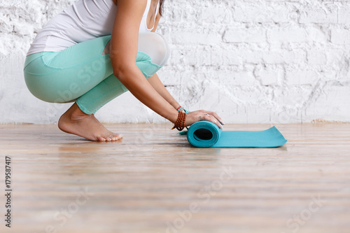 Fotografia  Close-up of attractive young woman folding blue yoga or fitness mat after working out at home in living room