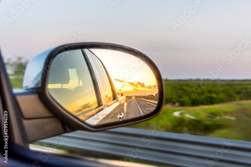 Photo Sunset Through Truck Rear View Mirror on the Highway