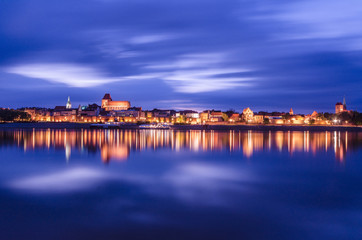 Torun at night. UNESCO-class medieval Old Town reflected in Vistula river, Poland. Europe.