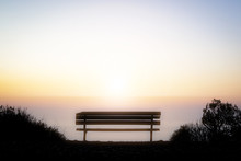 Empty Bench Overlooking The Colorful Light Of Sunset Over The Horizon Of The Pacific Ocean Off The Coast Of California