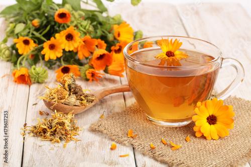 Obraz Calendula tea with fresh and dried flowers on white wooden background - fototapety do salonu