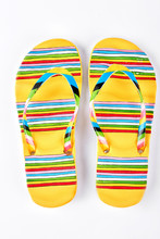Summer Fashion Striped Slippers. Yellow Flip Flops In Colorful Stripes Isolated On White Background. Fashion Beach Footwear.