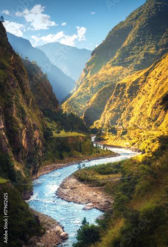 Niesamowity krajobraz z wysokimi himalajskimi górami, piękną zakrzywioną rzeką, zielonym lasem, niebieskim niebem z chmurami i żółtym światłem słonecznym jesienią w Nepalu. Górska dolina. Podróżuj w Himalajach. Natura