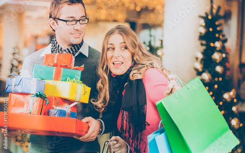 Plakat Para - mężczyzna i kobieta - z prezentami na Boże Narodzenie i torby na zakupy w centrum handlowym przed choinką
