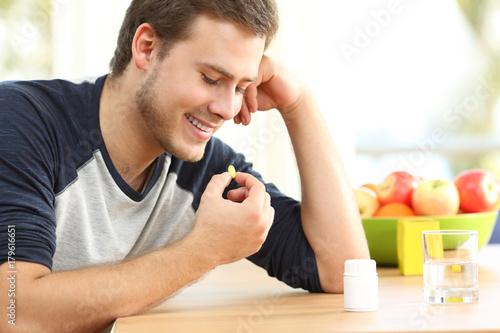 Fototapeta Happy man taking a vitamin pill at home obraz