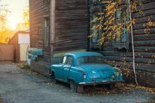 Old Vintage Car Near The Wooden Urban City.
