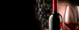 Wine. Bottle and glass of red wine with ripe grapes over black background