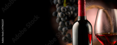 Fototapeta Wine. Bottle and glass of red wine with ripe grapes over black background obraz