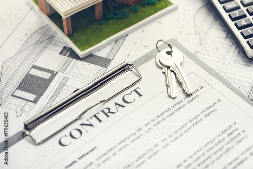A Mortgage Loan Contract Agreement With House Keys And Floor Plan
