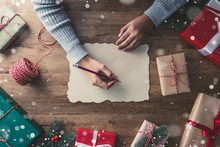 A Woman Writing On Craft Paper In The Center Of Christmas Gifts On A Wooden Table