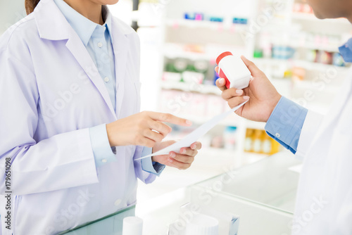 Pharmacists showing medicine bottle and discussing prescription drug in a pharmacy Canvas Print