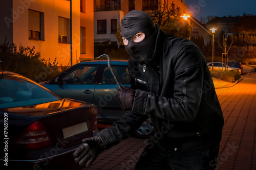 Photo Masked thief in balaclava with crowbar wants to rob a car