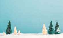 Small Green And White Christmas Trees In Snow